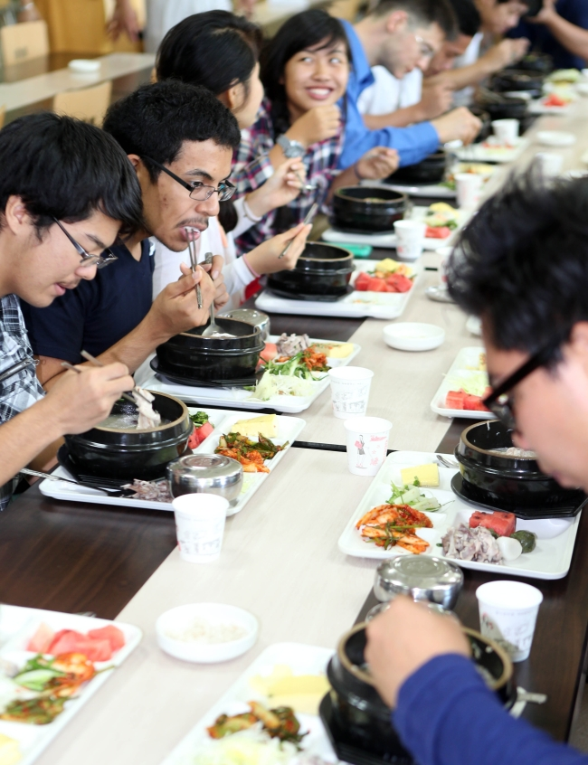 """Foreign exchange students of Tongmyong University in Busan eat samgyetang as part of """"Global Samgyetang Day"""" to introduce foreigners to Korean food. (Yonhap News)"""