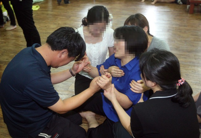 A teacher from the High School to the College of Education at Kongju University kneels Saturday in front of the families of five students who drowned Thursday while participating in a military-style camp in Taean, South Chungcheong Province. (Yonhap News)