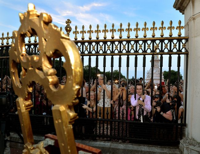 The large waiting crowds cheers as they read the news on an easel in the forecourt of Buckingham Palace, to announce the birth of a baby boy, at 4.24pm to the Duke and Duchess of Cambridge at St Mary's Hospital in west London, Monday July 22, 2013. The notification was set up on an easel facing the gates for public view. The child is now third in line to the British throne. (AP-Yonhap News)