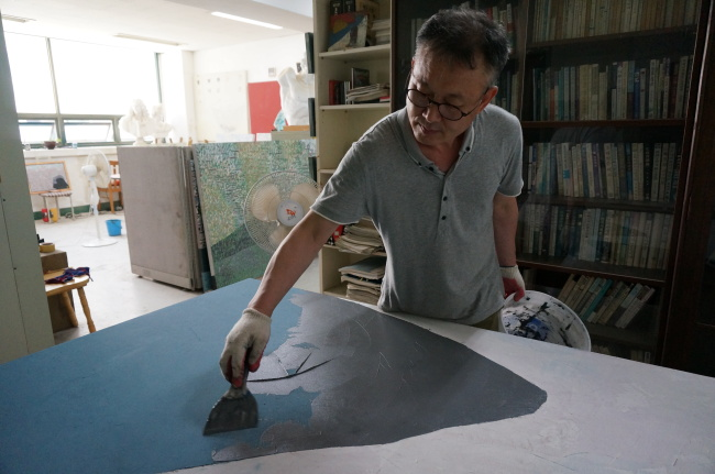 Artist Kim Jae-sin works on a new painting at his studio in Tongyeong, South Gyeongsang Province. (Lee Woo-young/The Korea Herald)