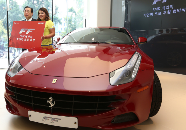 LPGA golfer Park In-bee and Forza motors Korea CEO Ahn Jong-won pose at a Ferrari dealership in Cheongdam-dong, southern Seoul, on Wednesday after the luxury sports carmaker offered the Ferrari FF for her use for the next year. ( Yonhap News)