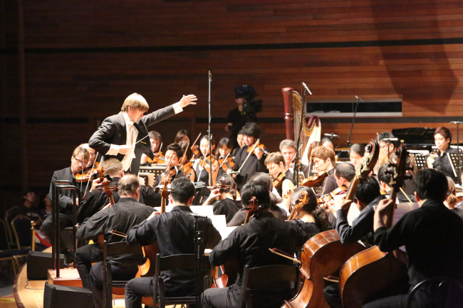 Conductor Sasha Makila leads the GMMFS Orchestra and The National Chorus of Korea in a performance at Alpensia Music Tent in Pyeongchang, Gangwon Province, Saturday. (GMMFS)