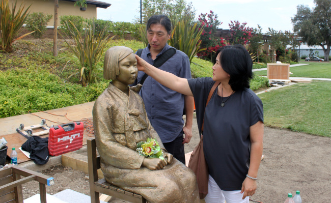 """Sculptors Kim Un-seong (left) and Kim Seo-kyeong make last-minute touches to the """"Statue of a Girl of Peace"""" in Glendale, California, Sunday. (Yonhap News)"""