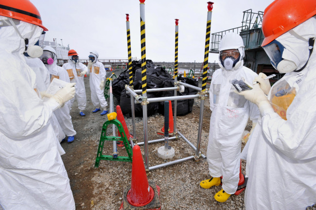 Reporters inspect an observation well which is dug to take underground water samples near Fukushima Dai-ichi nuclear plant Unit 1 of Tokyo Electric Power Co., in Okuma, Fukushima prefecture, northeastern Japan. (AP-Yonhap News)