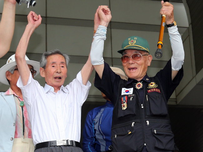 Yeo Yoon-taek (left) and Lee Choon-sik cheer at the Seoul High Court on July 10 after it ordered Nippon Steel and Sumitomo Metal to pay them compensation for forced labor during Japan's colonization of Korea. (Yonhap News)