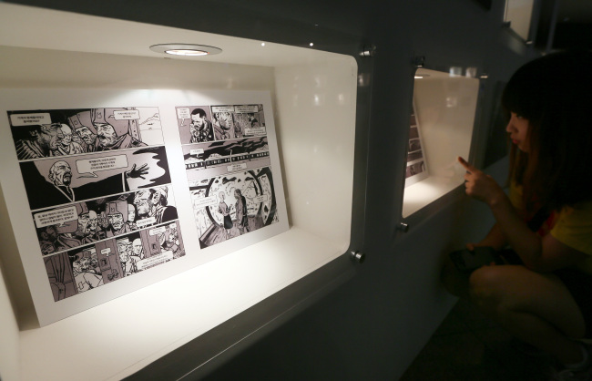 "A viewer reads the graphic novel ""Snowpiercer"" on display at the 16th Bucheon International Comics Festival. (Yonhap News)"