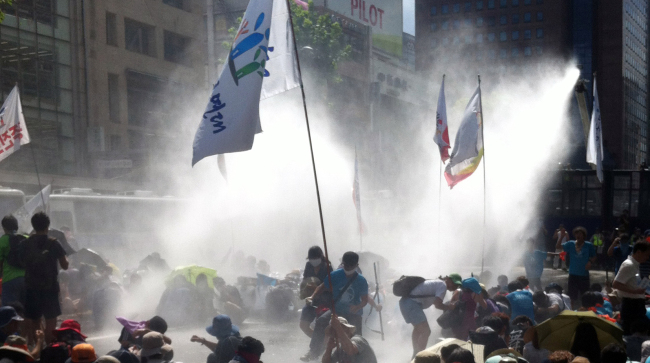 Police fire water cannon to break up a group of demonstrators who were illegally occupying roads in Jongno, central Seoul after a Liberation Day rally on Thursday. ( Yonhap News)