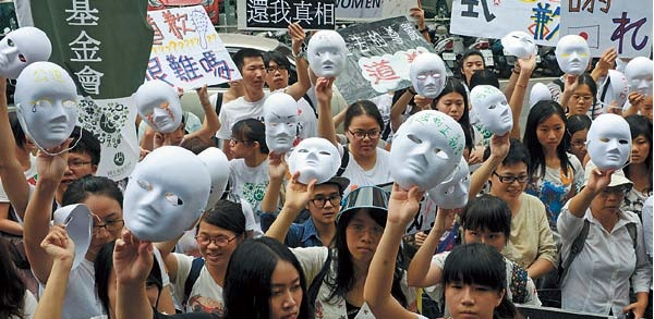 Supporters display masks as they demand an apology from Japan over the comfort women issue during a demonstration in front the Japan Interchange Association in Taipei on Wednesday. (AFP-Yonhap News)