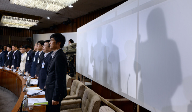 Former and current National Intelligence Service officials (behind the screen) swear an oath at a parliamentary probe into the spy agency's alleged election interference at the National Assembly on Monday. (Park Hyun-koo/The Korea Herald)