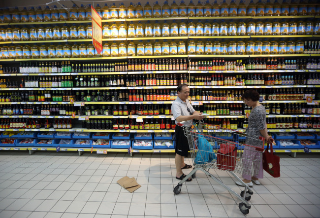 Shoppers browse in front of bottles of oil displayed at a store in Shanghai, China. (Bloomberg)