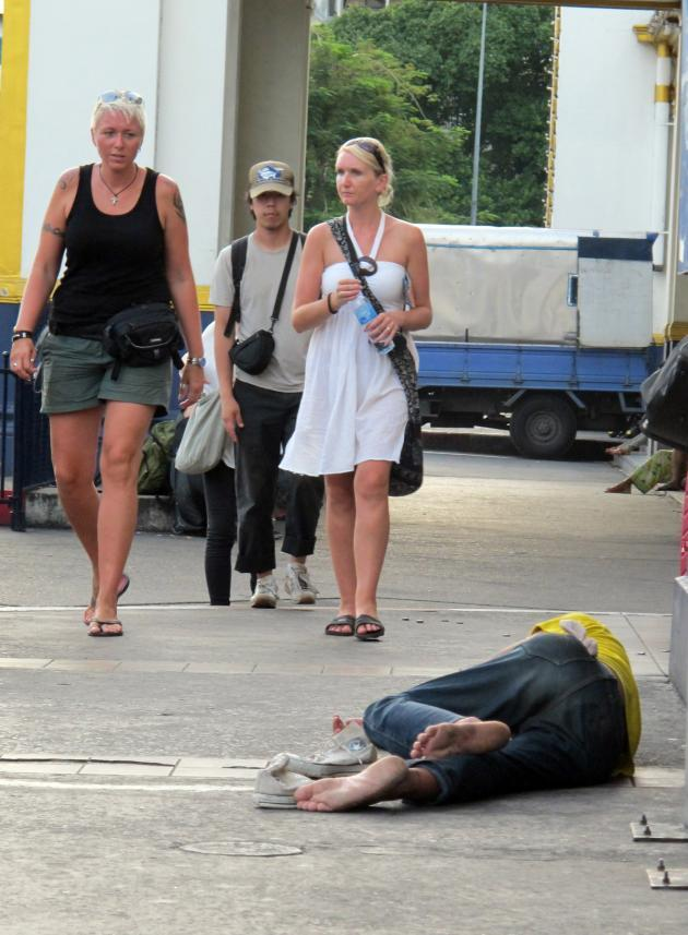 A homeless man lies on the street in Thailand. (The Nation)