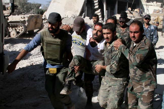 In this photo taken on a government organized tour, Syrian army soldiers evacuate a comrade injured during heavy clashes with Syrian rebels in the Jobar neighborhood of Damascus, Syria, Saturday. (AP-Yonhap)