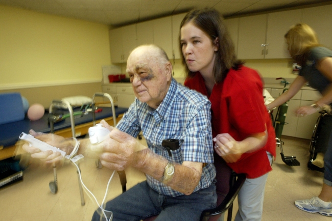 A therapist assists Charles Huska as he plays a boxing game on the Wii game console in Kansas City, Missouri. (MCT)