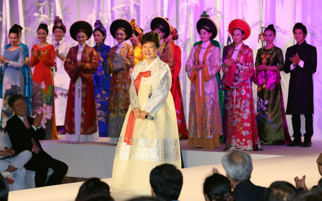 President Park Geun-hye attends a fashion show featuring the traditional dresses of Korea and Vietnam -- the hanbok and the ao dai -- in the Vietnamese capital of Hanoi on Sunday. (Yonhap News)