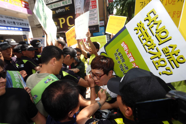 Members of a labor union for part-time workers protest for a higher minimum wage in Seoul last month. (Yonhap News)