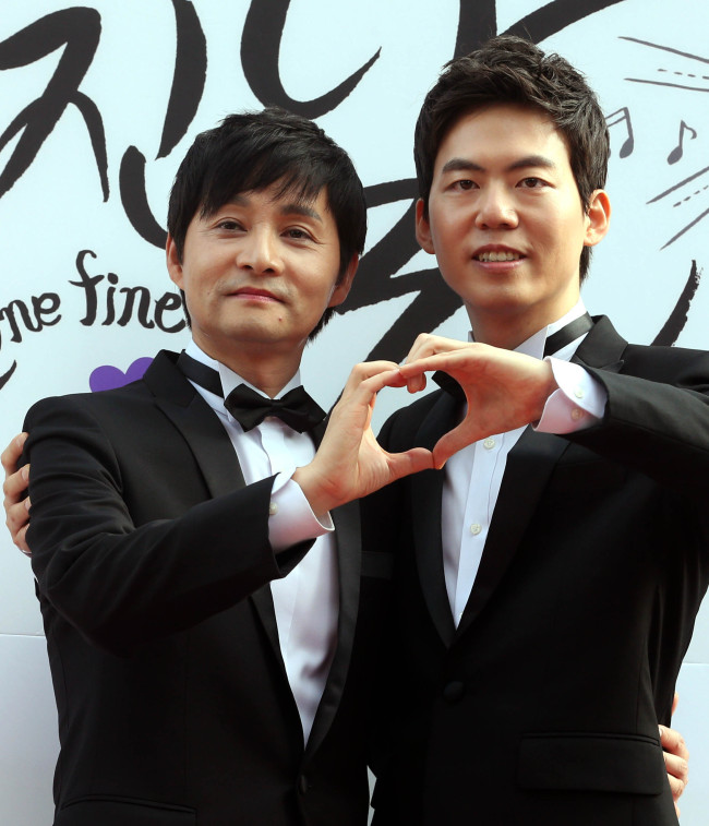 Film director Kim-Jho Gwang-soo (left) and his partner Kim Seung-hwan pose for photo before their wedding ceremony held in Seoul, Saturday. (Yonhap News)