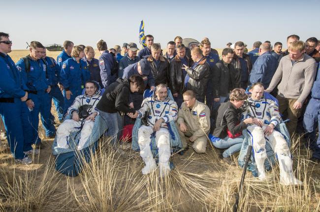 Astronauts Chris Cassidy (from left), Pavel Vinogradov and Alexander Misurkin sit in chairs shortly after landing in Zhezkazgan, Kazakhstan, Wednesday. (AP-Yonhap News)