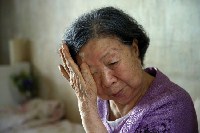 A South Korean elderly woman who was to meet her seperated family in North Korea wipes her tears after Pyongyang postpones the reunions.(Yonhap News)