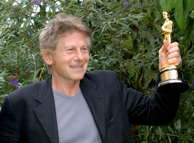 "Film director Roman Polanski holds his Best Director Oscar for ""The Pianist"" in Deauville, France, in 2003. Polanski could not attend the Oscar ceremony because he was facing arrest in the United States. (MCT)"