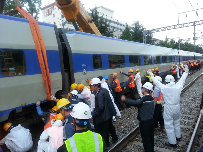 Employees work at the crash site of a three-way train collision outside Daegu Station last month.(Yonhap News)