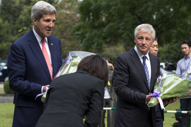 "A woman bows to U.S. Secretary of State John Kerry (left) and U.S. Secretary of Defense Chuck Hagel, as they participate in a ""wreath laying"" ceremony at Chidorigafuchi National Cemetery in Tokyo on Thursday. (AP-Yonhap News)"