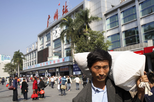 Migrant workers walk outside the main train station in Guangzhou, China. (Bloomberg)