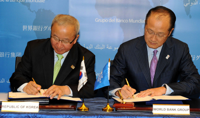 Finance Minister Hyun Oh-seok (left) and World Bank president Jim Yong Kim sign an agreement at the World Bank's headquarters in Washington D.C. on Thursday for the opening of a regional office of the World Bank in Songdo, west of Seoul, in December. (Yonhap News)