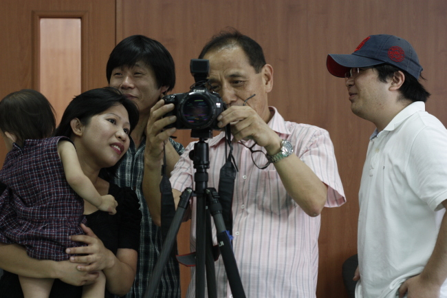 Han Yong-oe (center), founder of Inclover, a social welfare foundation for multicultural families, looks at a portrait of a multicultural family after taking their picture.