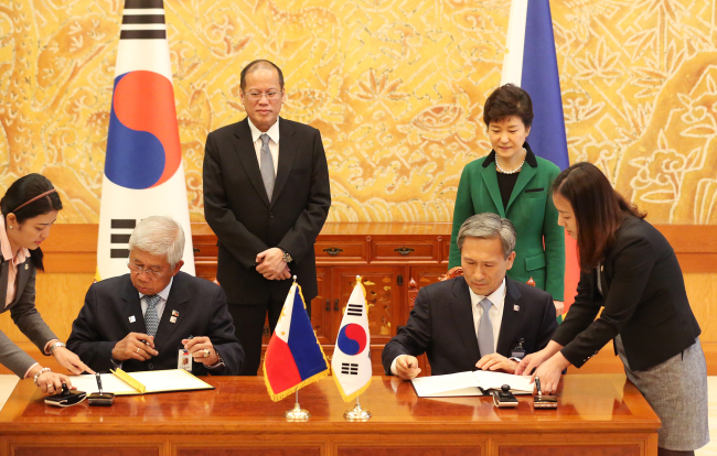 Presidents Park Geun-hye and Benigno S. Aquino III of the Philippines watch Defense Minister Kim Kwan-jin (right) and the Philippines Defense Secretary Voltaire Gazmin sign a memorandum of understanding on bilateral defense cooperation at Cheong Wa Dae on Thursday. (Yonhap News)