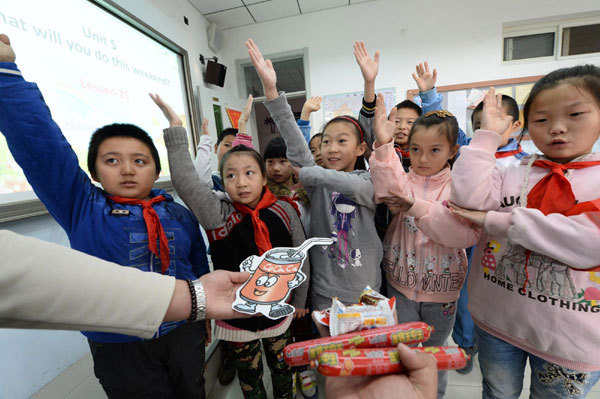 School children practice English in Beijing on Wednesday. (China Daily)