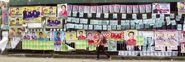 A man walks past campaign posters of candidates in Monday's barangay elections in Quezon City.(Philippine Daily Inquirer)