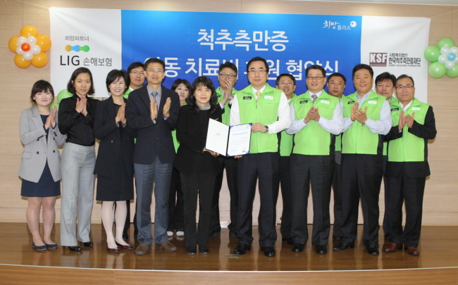 LIG Non-life Insurance CEO Kim Byeong-heon (fourth from right, front) and Korea Scoliosis Foundation chairwoman Cheon Eun-mi hold an agreement to sponsor medical expenses for scoliosis patients at Chungeum Hall in Seoul on Monday. (LIG Non-life Insurance)