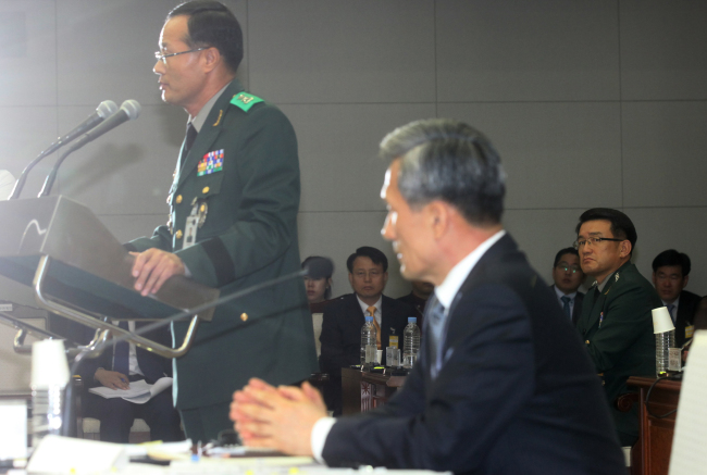 The Defense Ministry's Criminal Investigative Command chief Maj. Gen. Baek Nak-jong (standing) answers questions from lawmakers during a parliamentary audit last week, also attended by Defense Minister Kim Kwan-jin (center) and Defense Security Command chief Lt. Gen. Lee Jae-su (right). (Yonhap News)
