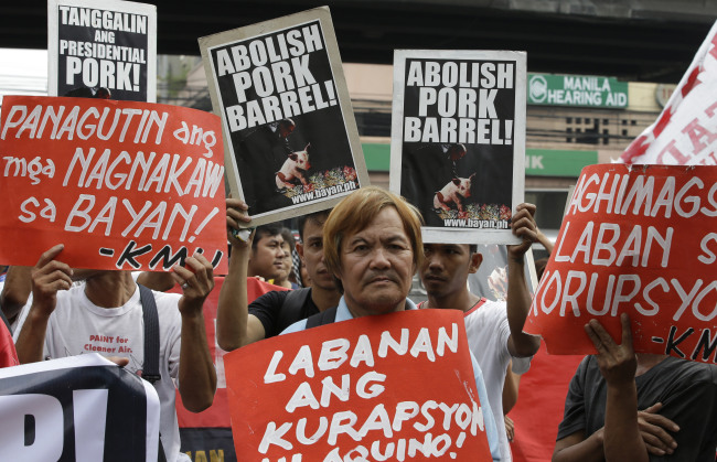 """Protesters display placards during a rally at the Philippine Supreme Court to coincide with the oral arguments on the controversial government funds intended for development projects by lawmakers known as """"Pork Barrel"""" in Manila, Philippines. (AP-Yonhap News)"""