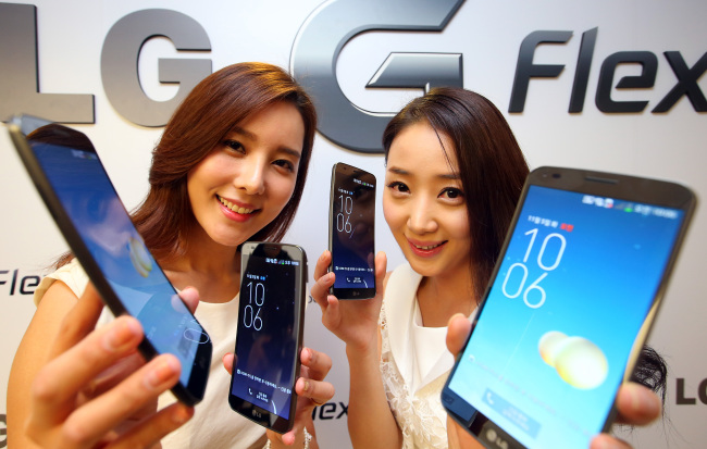 Models pose with LG Electronics' first curved smartphone, the G Flex, at the phone's unveiling in Seoul, Tuesday. (LGE)