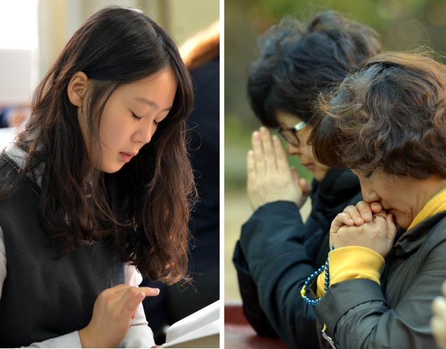 A student sits for the College Scholastic Ability Test at a high school in Seoul while parents of students taking the annual college entrance examination pray at Myeongdong Cathedral on Thursday. (Kim Myung-sub/The Korea Herald)