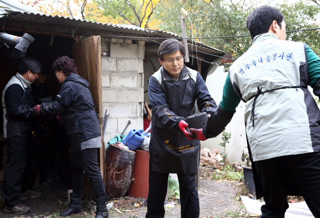 Minister of Justice Hwang Kyo-ahn (center) passes a charcoal brick to a ministry volunteer in a charitable event for seniors living alone in poverty in Dobong-gu, Seoul, Saturday. (The Ministry of Justice)