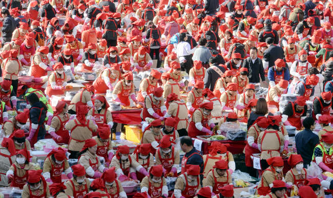 Some 3,000 volunteers make kimchi in a charity event hosted by Korea Yakult at Seoul Plaza on Wednesday. A total of 250 tons of kimchi they made will be distributed to about 25,000 underprivileged people. (Ahn Hoon/The Korea Herald)