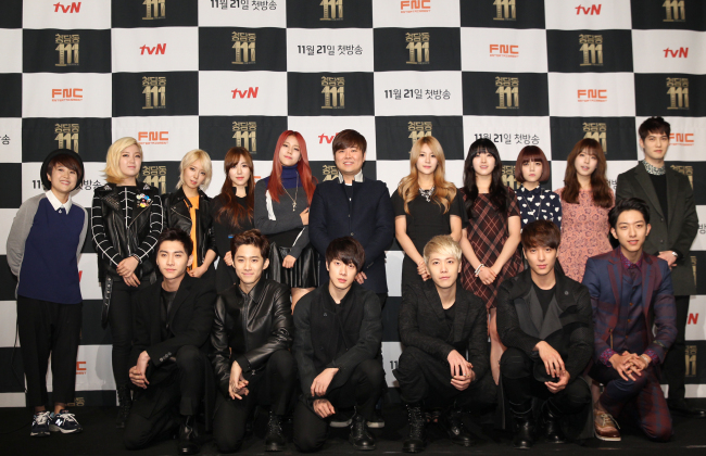 """FNC Entertainment CEO Han Sung-ho (center, second row) poses with members of the label's artists at the """"Cheongdamdong 111"""" press conference in Seoul on Monday. (CJ E&M)"""