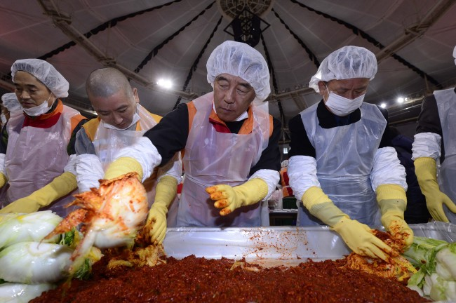 Kim Chang-geun (second from right), chairman of the Supex Council, SK Group's highest decision-making body, makes kimchi to donate to the needy in a group-wide event in a gymnasium at Olympic Park in Seoul on Tuesday. About 1,000 managers and union leaders of SK subsidiaries, chief executives of their suppliers and members of the Korea Council of Food Support volunteered to make kimchi with 45,000 cabbages. (Park Hae-mook/The Korea Herald)