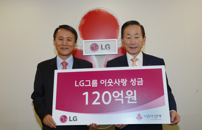 Kim Young-kee (left), executive vice president of LG Corp., who leads LG Group's Corporate Social Responsibility team, poses with Community Chest of Korea chairman Lee Dong-kurn after delivering 12 billion won to the charity in Seoul on Wednesday. (Chung Hee-cho/The Korea Herald)