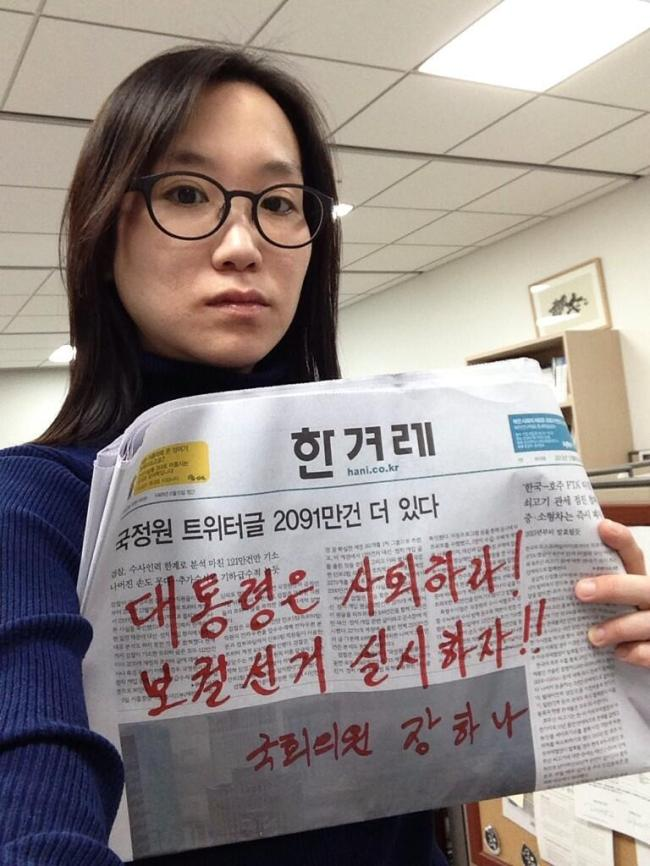 "Rep. Jang Ha-na holds up a newspaper on which she has written ""President resign! Let's hold a by-election"" in her office at the National Assembly in a photo she posted online Sunday. (Yonhap News)"