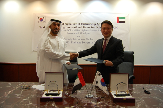 Icederby International president and CEO Hyun Do-jung (right) shakes hands with Saif Saeed Al Mazrouie, business office director of the Private Office of UAE Sheikha Sallama Bint Tahnoun Bin Mohammed Al Nahyan after signing an agreement on the joint launching of the 2020 Dubai Expo celebration event in Dubai on Thursday. (Icederby International)