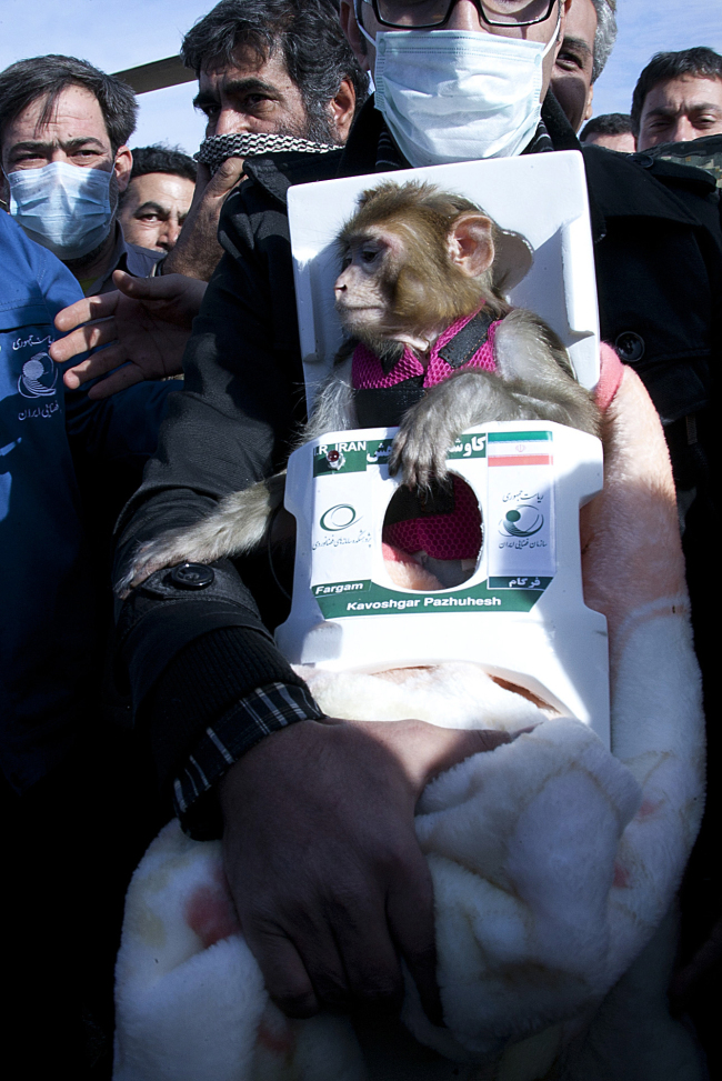 A man carries a monkey named Fargam during a mission to send it into space on Saturday. (AP-Yonhap News)