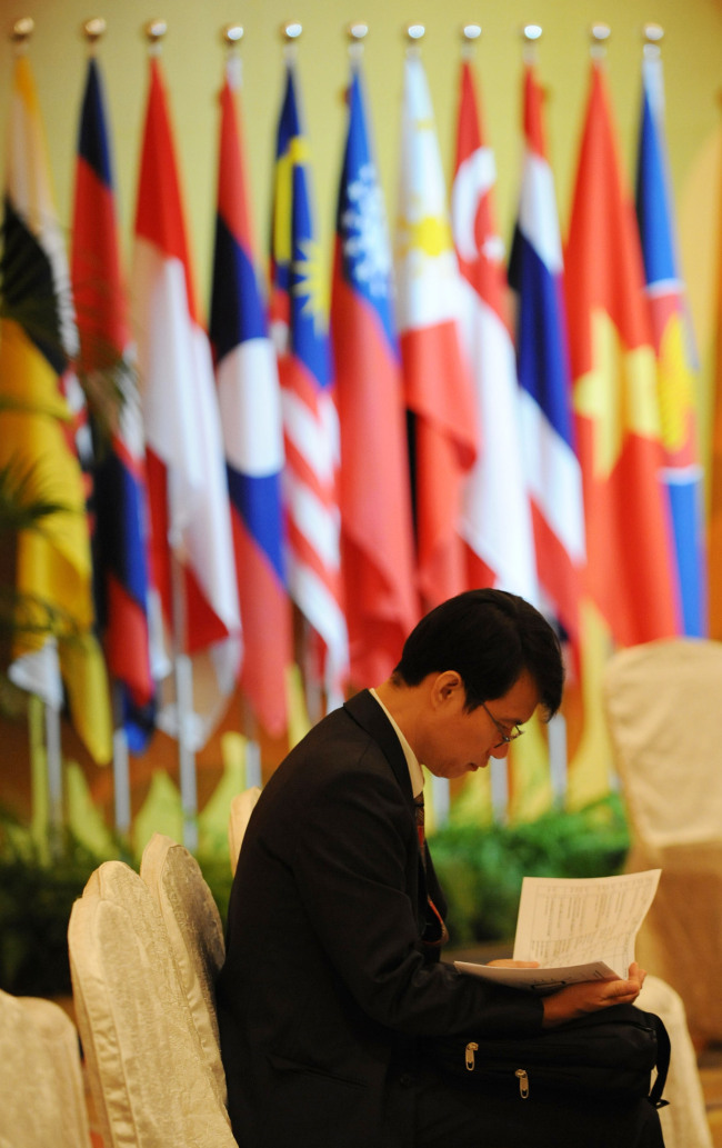 A delegate reads documents in front of flags of the Association of Southeast Asian Nations countries. (Bloomberg)