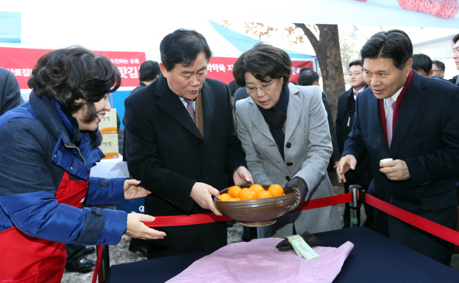Saenuri Party floor leader Choi Kyung-hwan (second from left) and Supreme Council member Lee Hye-hoon (second from right) admire a porcelain bowl donated by President Park Geun-hye at the party's charity bazaar in Seoul on Wednesday. (Yonhap News)