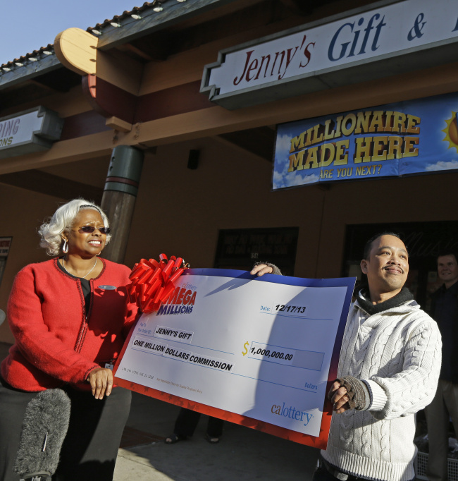 Jenny's Gift Shop owner Thuy Nguyen (right) accepts a $1 million check from California lottery sales representative Mona Sanders in San Jose, California, Wednesday. (AP-Yonhap News)