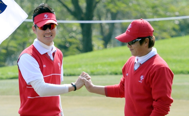 Kim Hyoung-sung (left) congratulates Kim Kyung-tae after he sinks the ball in for a birdie on Hole Two of the Asian Games Course at the Dragon Lake Golf Club on the first day of The Royal Trophy golf championship in Guangzhou, China on Friday. Ahn Hoon The Korea Herald