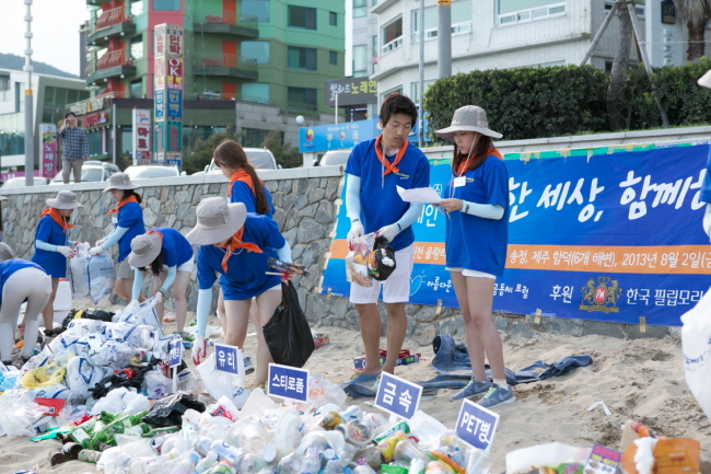 """Volunteers with Philip Morris Korea's """"Ocean Love Campaign"""" clean up the shoreline by picking up and sorting trash for proper recycling. (Philip Morris Korea)"""