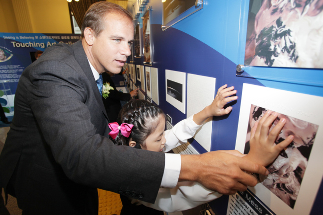 """Standard Chartered Bank Korea CEO Richard Hill helps a visually impaired child experience a custom-made rendition of an artwork at the company's """"Touching Art Gallery"""" in Seoul. (SC Bank Korea)"""